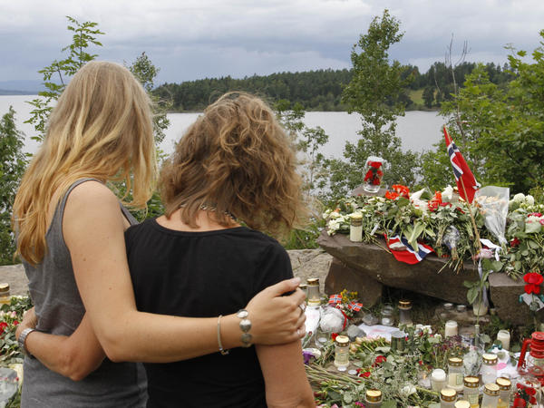 Two young women stand in silence after placing flower near Sundvollen close to the Utoya island, near Oslo, Norway, Tuesday, July 26, 2011, where a gunman Anders Behring Breivik killed at least 68 people. The defense lawyer for the man who confessed to the mass killings told The Associated Press on Tuesday that there's no way his client will walk free and is likely insane.