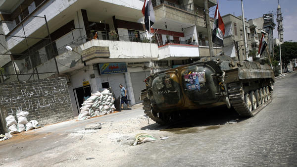 A Syrian military tank takes position in a residential street in the central city of Homs Monday. Government troops reportedly are defecting to join the activists.