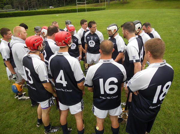 The Barley House Wolves circle up around their coach, Ruairi O'Mahony, for a  half-time huddle during a match against a hurling team from Worcester,  Mass.
