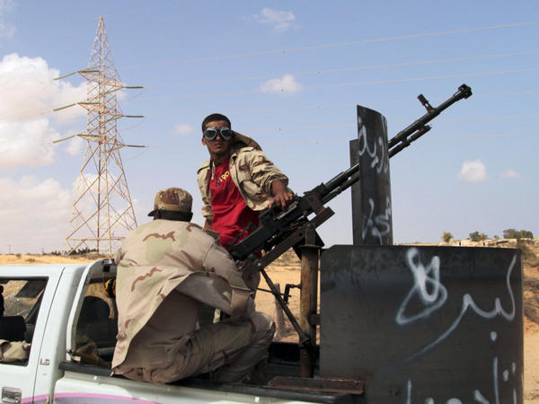 Revolutionary fighters drive up the western road entering  Sirte on Thursday. The rebels are playing a waiting game; they are set up outside the city but are not yet trying to advance.