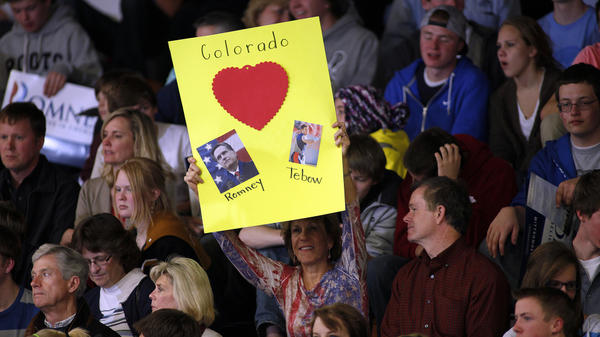 A Mitt Romney supporter holds up a sign showing her love for Romney and Denver Broncos quarterback Tim Tebow at a rally for the GOP presidential candidate at Arapahoe High School this week in Centennial, Colo.