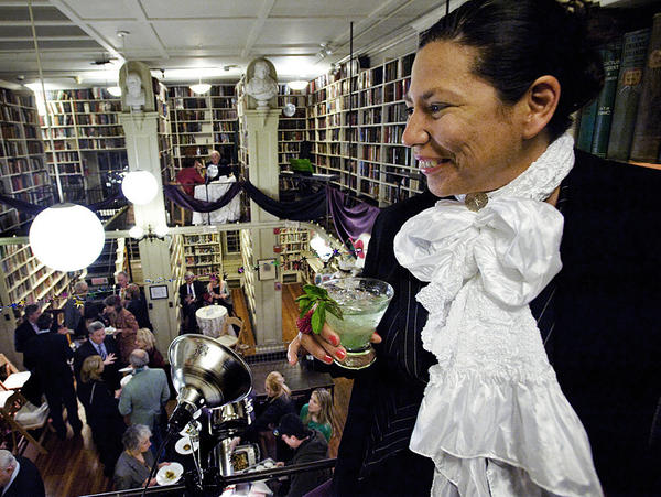 Chilean artist Magaly Ponce looks out from the mezzanine at the Oscar Wilde party at the Providence Athenaeum.