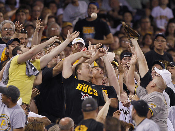 Pittsburgh Pirates fans reach for a foul ball hit into the stands by Mike Moustakas of the Kansas City Royals in the seventh inning of a game in Pittsburgh.