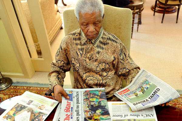 Mandela sifts through newspapers at his home in Johannesburg after casting his vote for local elections on May 16, 2011.
