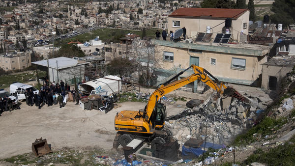 Israeli soldiers keep watch as a bulldozer demolishes a house belonging to a Palestinian resident in east Jerusalem on Feb. 13. Israel said the home was built without a permit.