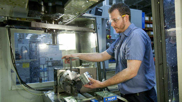 Brian Gasiewski removes the external housing for an industrial shock absorber from a CNC, or computer numerical control, machine at Fitzpatrick Manufacturing Co. in Sterling Heights, Mich.