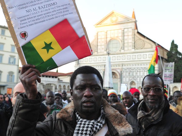 "A demonstrator holds a placard reading ""No to racism"" in front of Santa Maria Novella church in Florence, Italy, during a Dec. 17, 2010, anti-racism march in memory of two Senegalese men who were killed four days earlier by a far-right Italian."