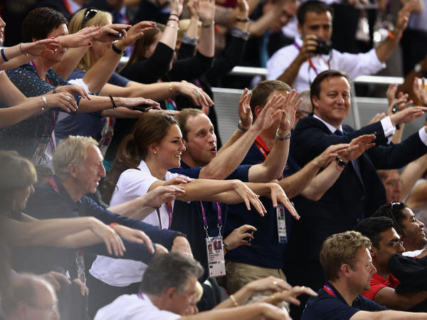 Prince William, his wife, Catherine, and Prime Minister David Cameron take part in the wave as they watch the track cycling at the London Games.
