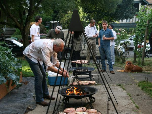 Ewald Mosel keeps the schwenkers swinging to ensure that the pork cooks evenly, while hungry guests look on.