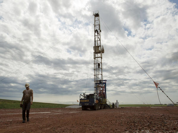 Austin Mitchell walks away from an oil derrick outside Williston, N.D., in July 2011. North Dakota is now the No. 2 producer of oil in the U.S. behind Texas.