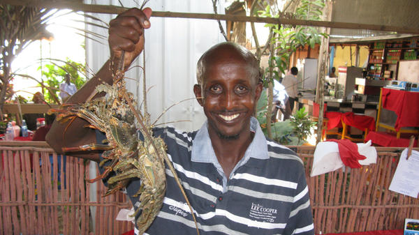 Somali chef Ahmed Jama holds up freshly caught spiny lobsters he's about to cook in one of his restaurants in Mogadishu.