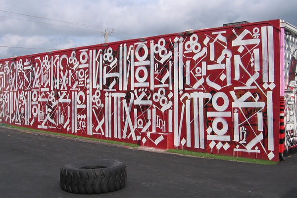 "Los Angeles artist RETNA developed his own alphabet from gang writing and calligraphy. The top line on this RETNA mural reads ""sacred dance of memories."""