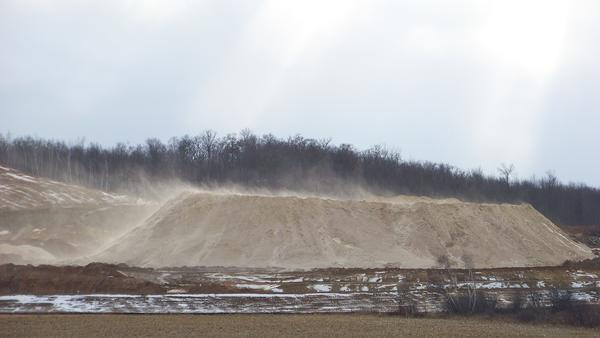 Dust blows off a pile of fracking sand at a mine near Chippewa Falls, Wis., on Dec. 15, 2011. Some of the air samples the National Institute for Occupational Safety and Health experts collected at fracking sites had such high levels of silica that the respirators typically worn by workers wouldn't offer enough protection, according to NIOSH standards.