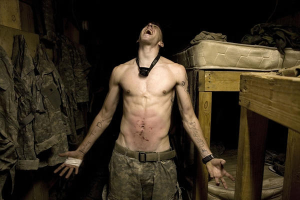 "Spc. Tad Donoho exhibits a ""pink belly,"" in which soldiers hit a colleague's stomach until it bruises for his birthday. ""[Photographer Tim Hetherington] had this tremendous interest in human beings,"" Sebastian Junger tells NPR's Renee Montagne. ""In some ways, the photography wasn't even the point. What he really wanted to do was engage with people ... and as a result his work was phenomenal."""