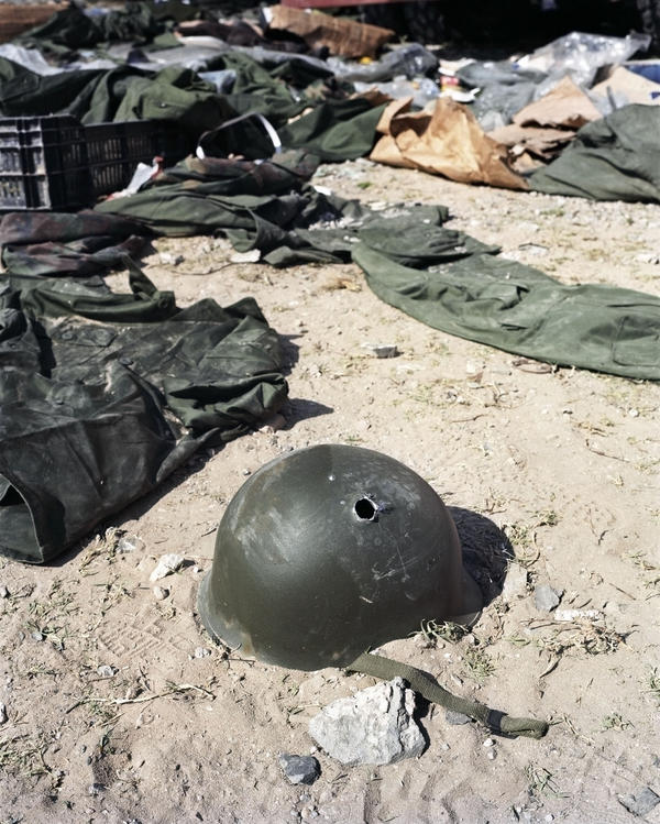 Hetherington's last photograph, taken April 20, 2011, the day he was fatally injured in a rebel mortar attack. After hours of fierce fighting at Tripoli Street, rebels secured the area and found a truck full of loyalist army supplies. Photographers at the scene concluded that the hole in this helmet had been shot by rebel forces at close range as they vented their anger at regime forces.