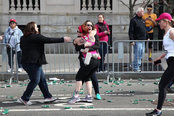 A runner embraces another woman on the marathon route near Kenmore Square on Monday in Boston.