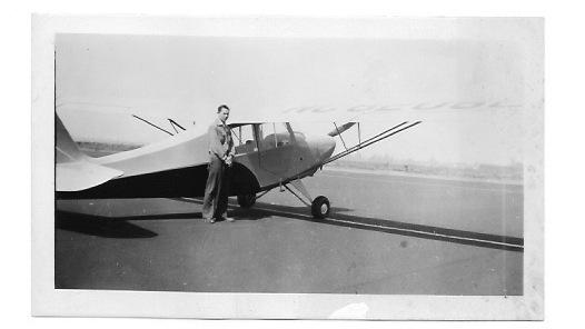 Louis Parsons in his late teens, circa 1946, standing beside an Aeronca Champion airplane, a typical trainer plane for aspiring post-war private pilots.