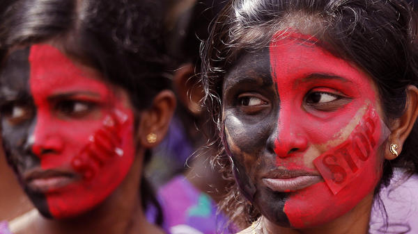 Two women in Colombo, Sri Lanka, attend a March protest calling for government action against domestic violence and rape.