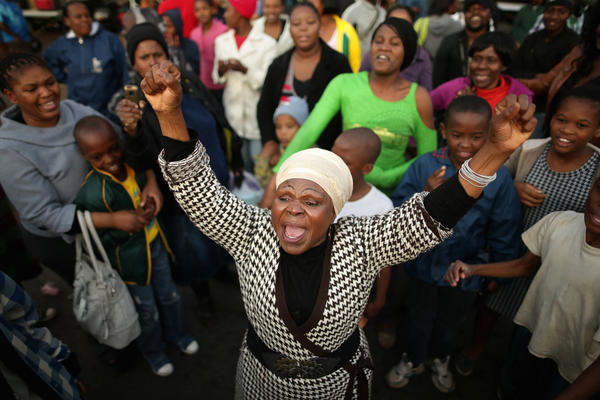 "Florence Nyadzani (center) leads people in song and cheers of support outside the hospital on June 25. ""I got my freedom because of Mandela,"" Nyadzani said. ""We pray every day because we love him."""