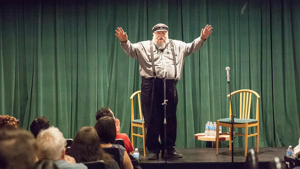 George R.R. Martin prepares to introduce author Neil Gaiman and performer Amanda Palmer at charity benefit at his newly renovated Jean Cocteau cinema in Santa Fe, N.M., on Sept. 29. Reopening the old movie house has been a passion project for the <em>Game of Thrones</em> author — but for some of his fans, it's one more distraction that's come between them and Martin's unfinished epic.