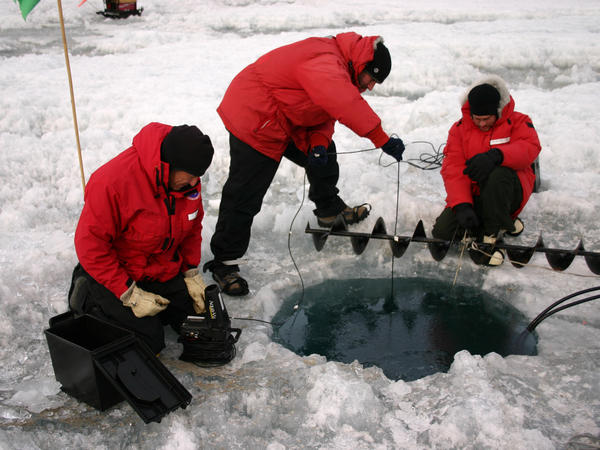 John Priscu, Phil Lee and Mike Lizotte use an underwater camera to check the progress of a hole being melted on Lake Bonney, Antarctica, in 2008.