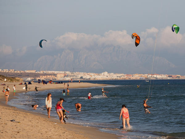 Bathers enjoying the beach while Africa is seen in the distance on Aug. 30, in Tarifa, Spain. Thousands of African migrants have landed in Tarifa, on flimsy boats that make the dangerous journey across the Straits of Gibraltar, from Morocco.