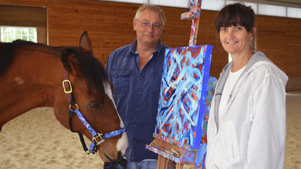 Metro Meteor, a retired racehorse, stands with owners Ron and Wendy Krajewski and one of his paintings at Motters Station Stables in Rocky Ridge, Md., earlier this year.