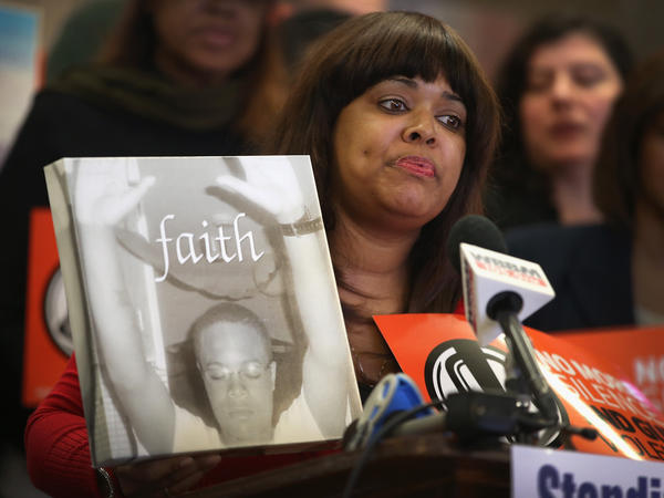Shundra Robinson holds a picture of her son, a victim of gun violence, at a gathering in Chicago on the anniversary of the shootings at Sandy Hook Elementary in Connecticut.