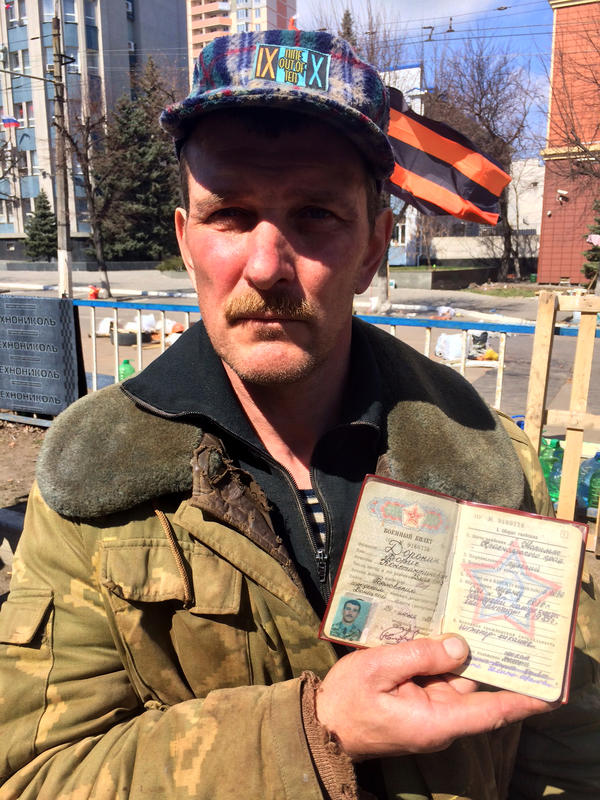 Boris Daronin is one of the activists manning the barricades in Luhansk. He holds up his ID card to show that he was in the Soviet army.