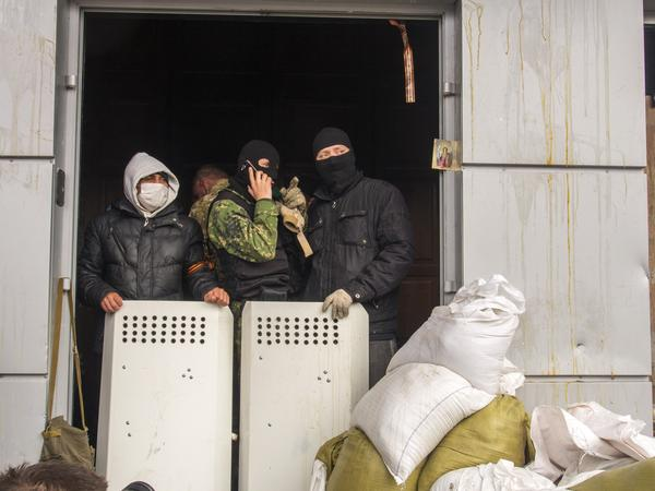 Masked pro-Russia activists guard an entrance to the Ukrainian regional office of the Security Service in Luhansk, 20 miles west of the Russian border, in Ukraine, on Wednesday.