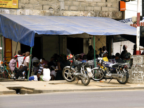 Pentecostal worshipers sit at Ministry Faith Banner's overflow section on a street corner in Douala.