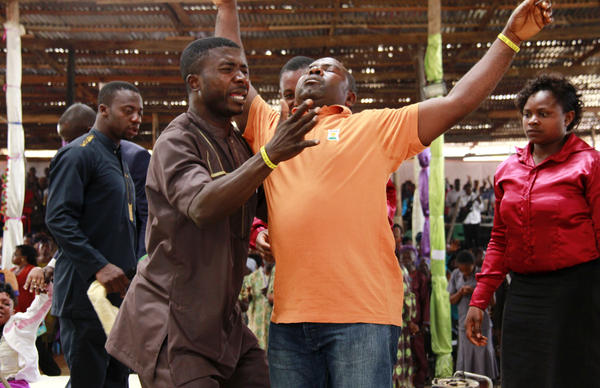 The Rev. Warah Solomon prays over a man at the Ramah Christian Center in Bamenda, northwest Cameroon. The country's has more than 500 Pentecostal churches like this one, which hosted nearly 5,000 worshipers on a recent Sunday.