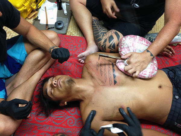 "Keone Nunes, a Native Hawaiian tattoo artist, says prayers to ""awaken"" the tattoo tools and bless the ink. Two ""stretchers"" pull the skin tight on the chest of Kaiola Farin to enable Nunes to tap straight lines."