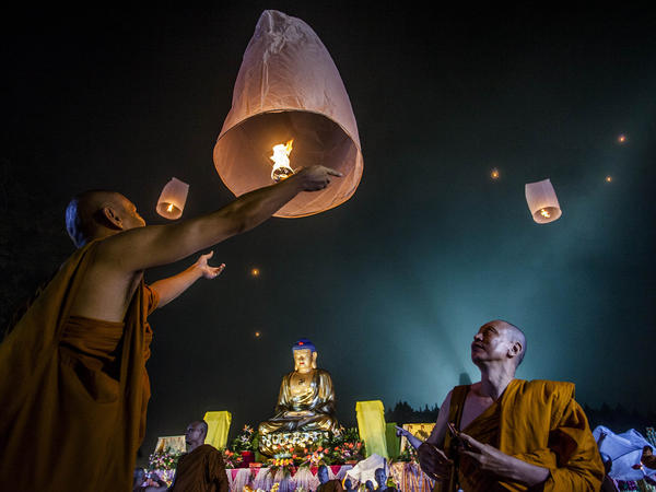 Buddhist monks release a lantern into the air at Borobudur temple in Magelang, Central Java, Indonesia. Where does their tradition fit into the science vs. religion debate?