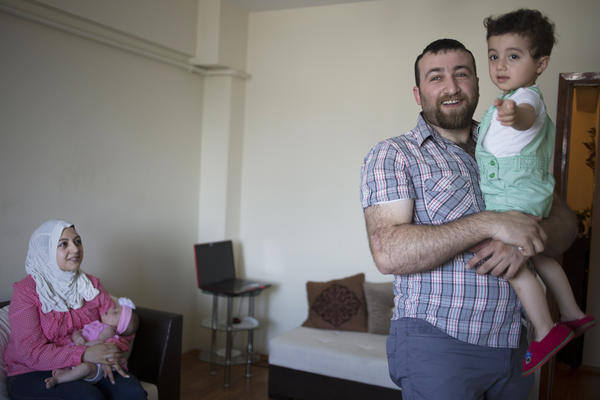 Mohamed's wife, Ghalia, holds their infant daughter, Leen, who was born in Turkey and is unregistered. Their son, Taim, now 2, was born in Syria, and his birth was documented there.