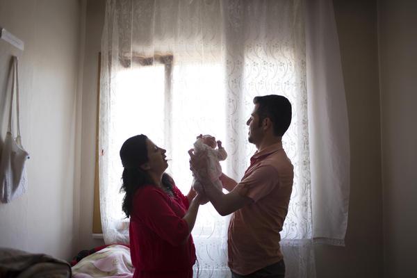Ayaman with his wife, Selma, and their 1-month-old daughter, Shana, who was born in Turkey. Syrian refugee parents who give birth in Turkey are finding it difficult to register their newborns, and many are stateless.
