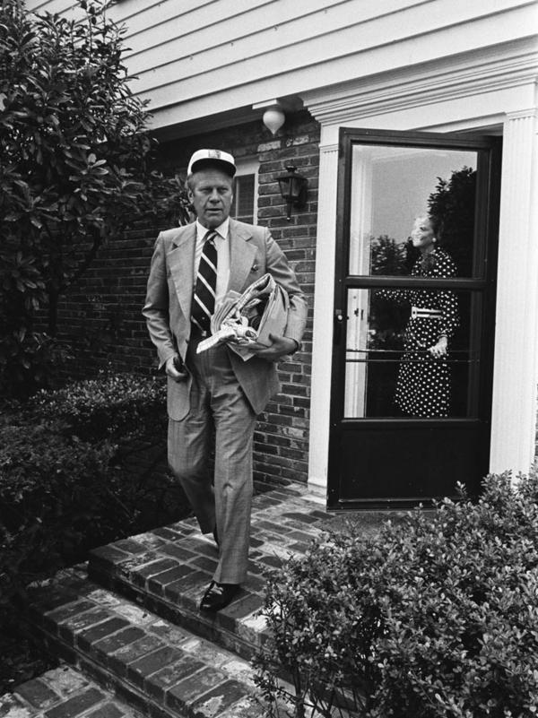President Gerald Ford walks out of his house in Alexandria, Virginia with First Lady Betty Ford in the doorway on August 18, 1974, having concluded his first week in office.