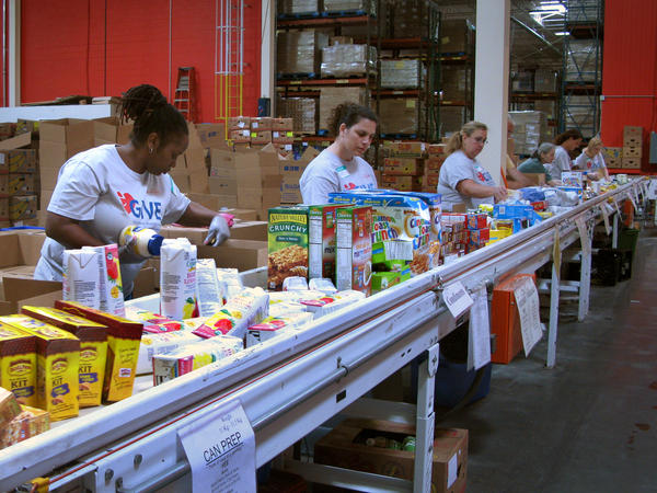 Volunteers at the Maryland Food Bank in Baltimore sort and box food donations on a conveyor belt. The bank started working with groups like the USO in 2013 to provide food aid to families affiliated with nearby military bases.