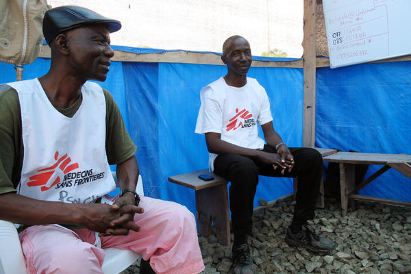 Counselors Moses Follay (right) and Prophet Muhammed Sano try to ease the stresses of Ebola patients and their family members.