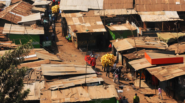 A man carries old plastic containers in March 2012 through the Kibera slum in Nairobi, Kenya. Kenyans living in poverty often collect plastics that they can turn into cash by taking it to companies that recycle it.