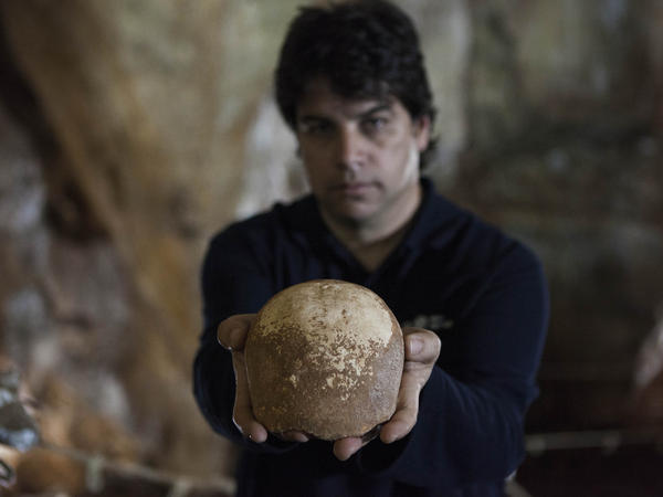 Dr. Omry Barzilai of the Israel Antiquities Authority holds an ancient skull found inside a cave near the northern Israeli city of Nahariya.