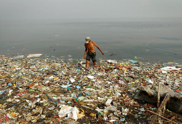 A fisherman collects water on a beach littered with trash at an ecological reserve south of Manila in 2013.