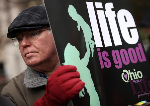Abortion-rights opponent Brian Normile of Beavercreek, Ohio, holds up a poster during a prayer vigil outside Planned Parenthood in Washington, D.C., in January.