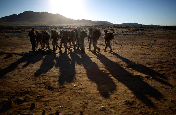 Male and female Marines hike up to a range at Twentynine Palms, a training base in the Mojave Desert, to participate in a live-fire exercise.