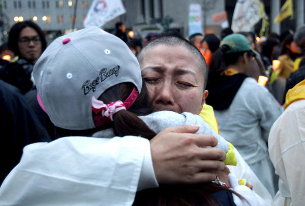 A relative of a victim of the Sewol ferry receives a hug during a rally earlier this month in Seoul. A year after the disaster that killed 304, parents of the victims are still demanding an independent investigation and recovery of the boat.