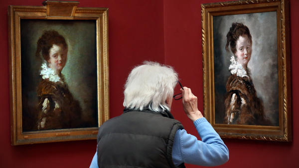 A visitor views a replica of Jean-Honore Fragonard's 18th century painting, <em>Young Woman </em>(right) as the original hangs to its left.