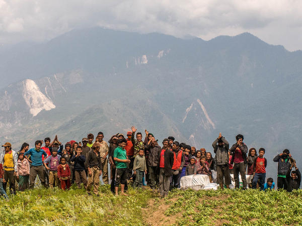 Nepalese villagers wave after collecting aid dropped by an Indian helicopter in Khanigaun, Nepal.