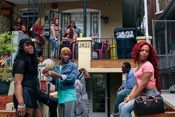 Ruby Corado (top, center) sits on the porch of Casa Ruby, a drop-in and service center for transgender people in Washington, D.C., while many of her clients, friends and employees hang out in front.  Corado also runs another venue nearby, a house for homeless transgender adults.