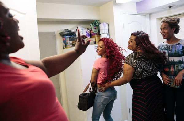 Ruby Corado, second from right, and Selena Cruz whip their hair around playfully while joking with Lazema Mills, left, and Giselle Gartzog, right, at Casa Ruby, a drop-in and service center for transgender people in Washington, D.C. Through the center, Corado helps people find housing, medical care and get food.