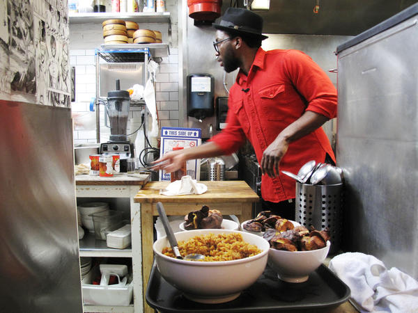 Tunde Wey gets ready to serve plantains and Jollof rice at his pop-up Nigerian dinner in the kitchen of Toki Underground, a ramen restaurant in Washington, D.C., in December 2014.